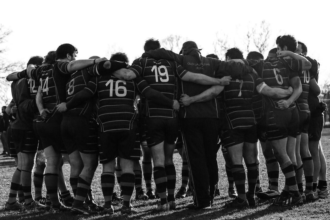 Jogadores de rugby abraçados em circulo de costas com vestimentas típicas. A foto está em preto e branco